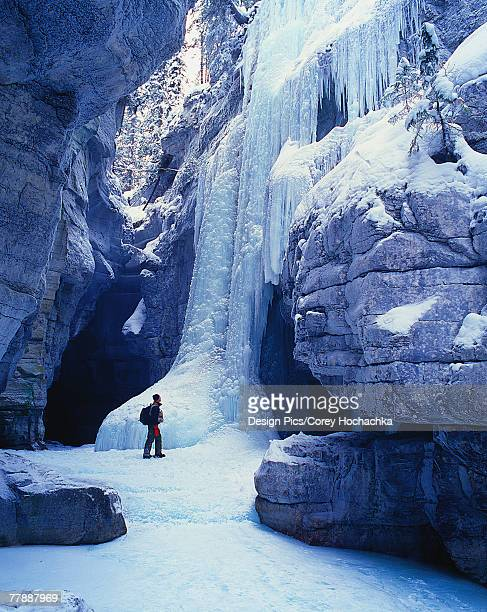 Hiker at base of ice cliff
