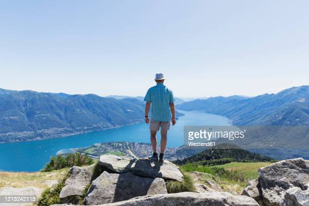 hiker at cimetta mountain top looking towards lago maggiore and ascona, locarno, ticino, switzerland - ascona stock pictures, royalty-free photos & images