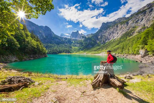 hiker at gosausee with dachstein view - austria stock photos and pictures