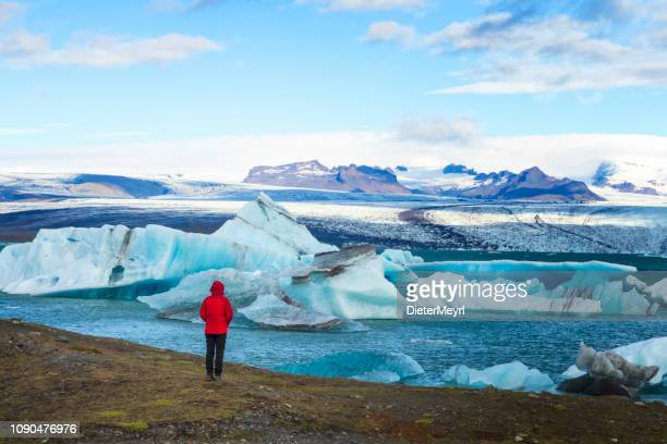 hiker at jökulsarlon glacier lagoon, iceland - glacier lagoon stock photos and pictures