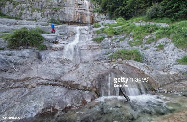 hiker at königsbach waterfall in nationalpark berchtesgaden - berchtesgaden stock photos and pictures