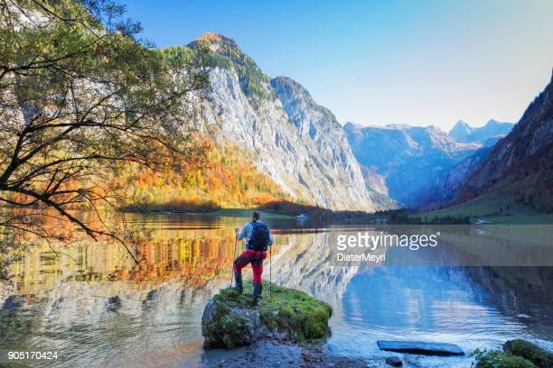hiker at lake königssee in nationalpark berchtesgaden - berchtesgaden alps stock photos and pictures