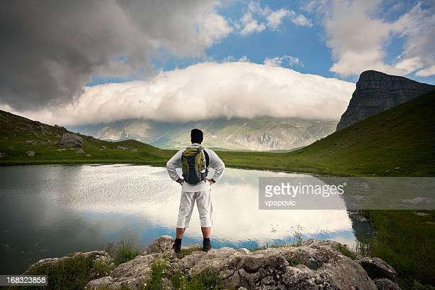 Randonneur sur lac entouré par les montagnes