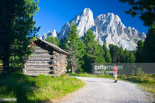 Hiker at Passo delle Erbe, between the Val di Funes and Val Badia, looking at peak of Sas de Putia in the Parco Naturale Puez-Odle, Dolomites.