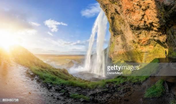 Wanderer am Wasserfall Seljalandsfoss in Island