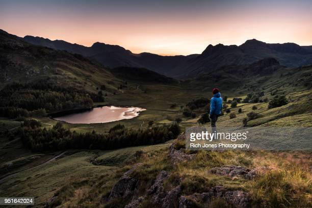 hiker at sunset in the english lake district - lake district stockfoto's en -beelden