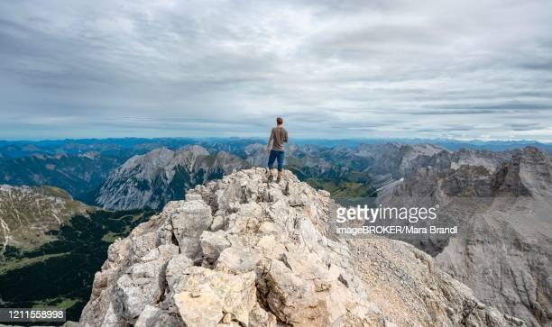 hiker at the summit of the birkkarspitze, hinterautal-vomper chain, karwendel, tyrol, austria - karwendel mountains stock pictures, royalty-free photos & images