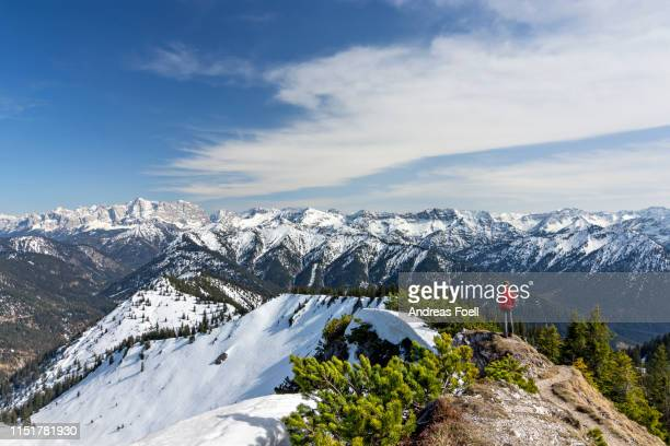 hiker at top of a mountain enjoying view in the ammergau alps (tirol, austria). landscape with mountains, snow and forest. - andreas solar stock pictures, royalty-free photos & images