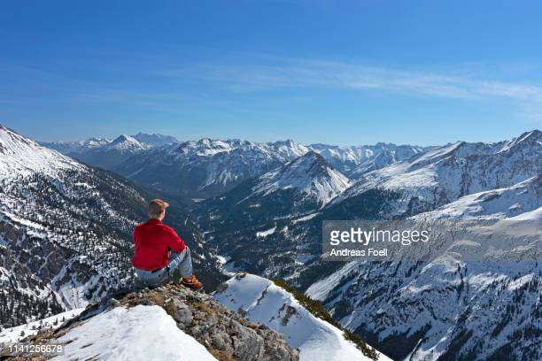 hiker at top of a mountain in winter enjoying the view - andreas solar stock pictures, royalty-free photos & images