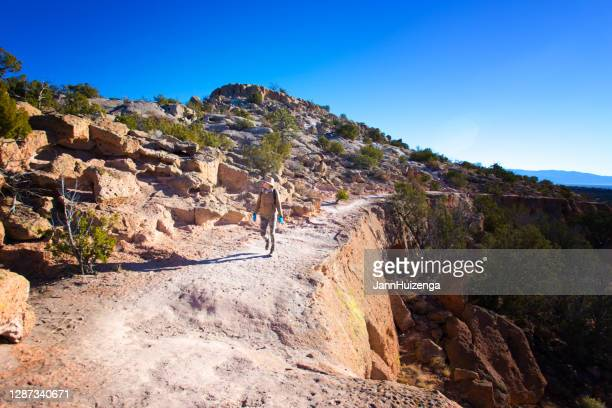 hiker at tsankawi trail, bandelier national monument, nm - santa fe new mexico stock pictures, royalty-free photos & images