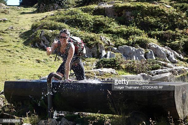 Hiker at water well at Ahornboden, Karwendel, Tyrol, Austria