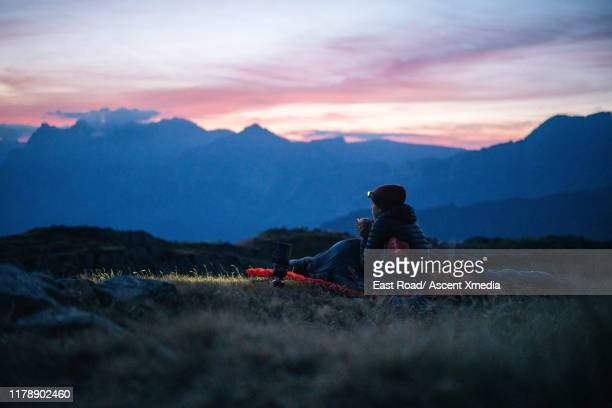hiker camps out in high mountain landscape - illuminated stock pictures, royalty-free photos & images