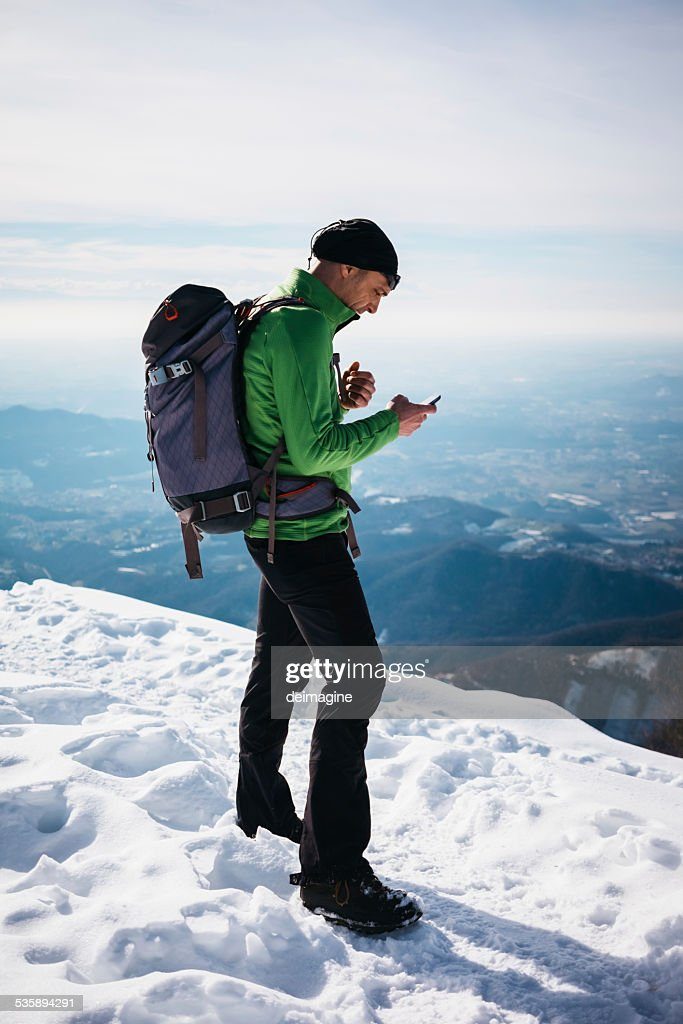 Hiker checking his smartphone : Stock Photo