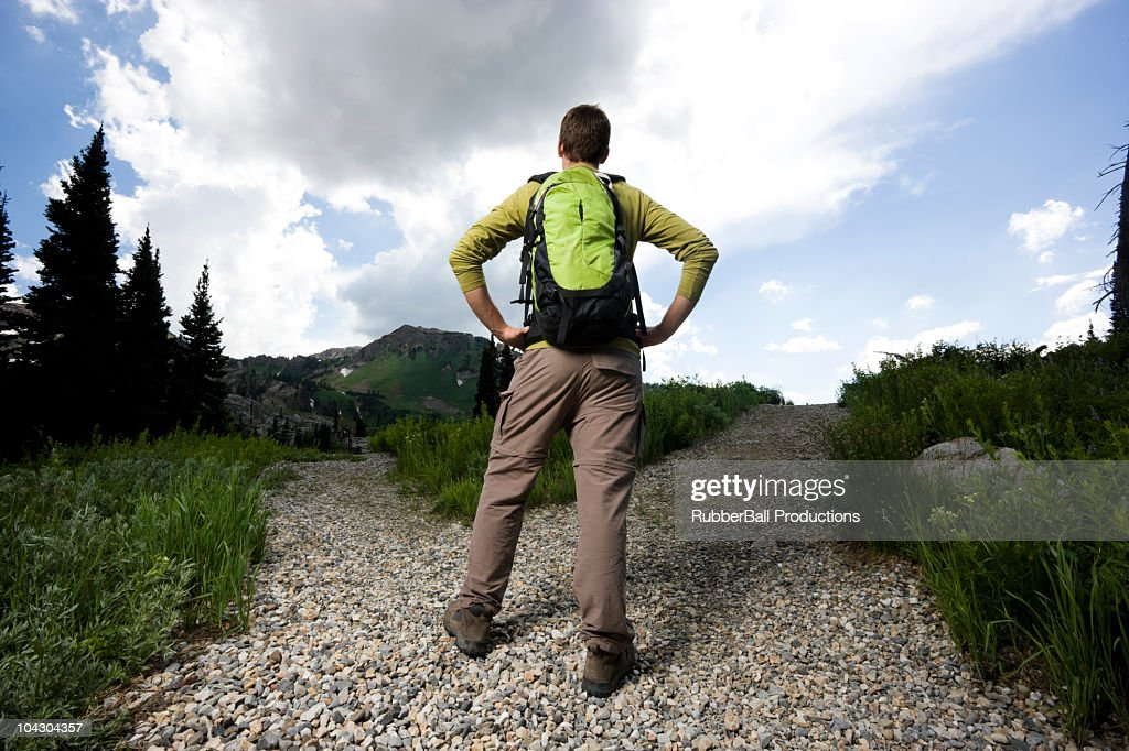hiker choosing which path to take : Stock Photo