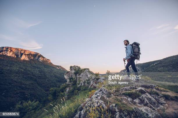 hiker climbing on the mountain - endurance stock photos and pictures