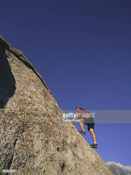 Hiker climbing rock at Alabama Hills , California