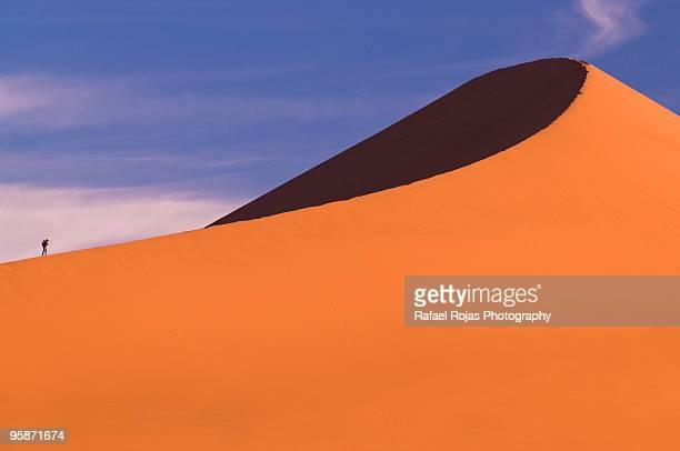 Hiker climbing sand dune in Sossusvlei, Namibia
