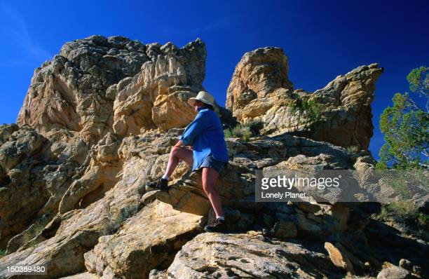 A hiker climbs one of the ancient rock formations in Grand Staircase National Park.