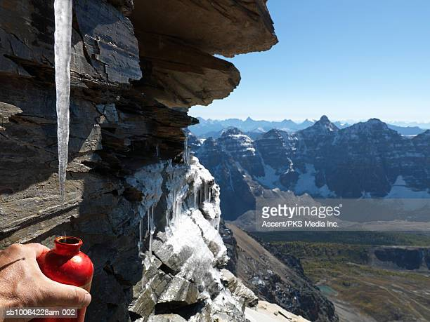 hiker collecting water from dripping icicle, valley of ten peaks in background - valley of the ten peaks stock pictures, royalty-free photos & images