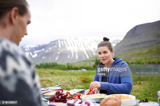 Hiker communicating with friend while having food