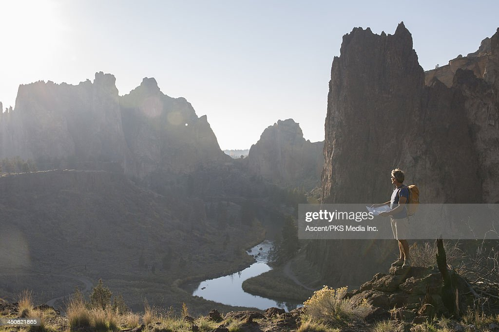 Hiker consults trail map, looks out to mtns, river : Stock Photo