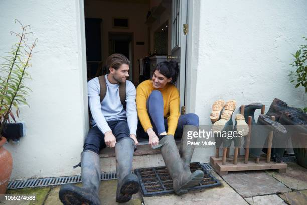 hiker couple on doorway putting on wellies - gummistiefel frau stock-fotos und bilder