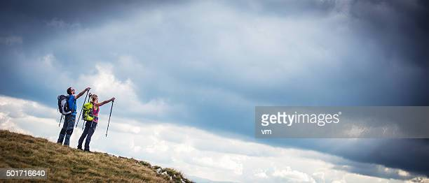 Hiker couple pointing at the cloudy sky