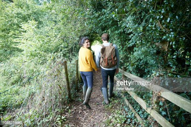 hiker couple walking in countryside - gummistiefel frau stock-fotos und bilder