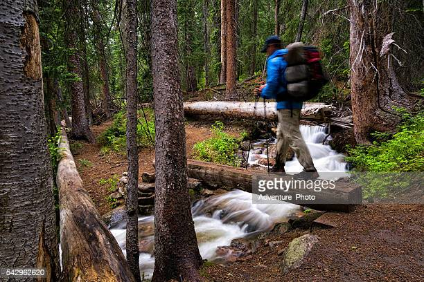 hiker crosses bridge over mountain creek - gore range stock photos and pictures