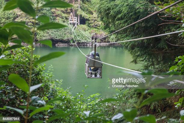hiker crosses river in a cable car, west coast trail, canada - vancouver island stockfoto's en -beelden