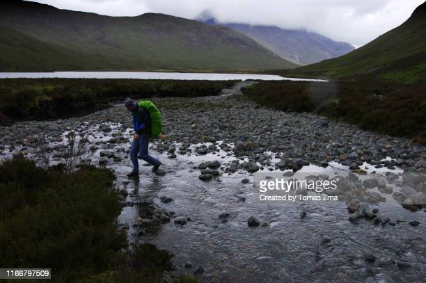 hiker crossing a water stream the wild valley of glen sligachan with surrounding peaks of the red hills - glen sligachan photos et images de collection