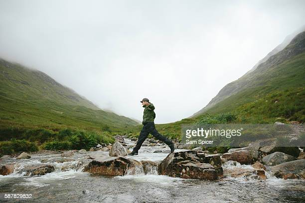 hiker crossing river in mountain valley, glencoe, scotland - scotland stock pictures, royalty-free photos & images