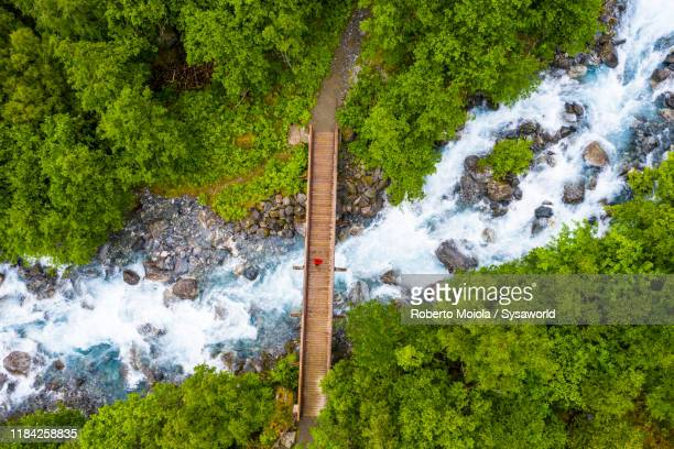 hiker crossing river towards mardalsfossen waterfall, norway - elevated walkway stock pictures, royalty-free photos & images