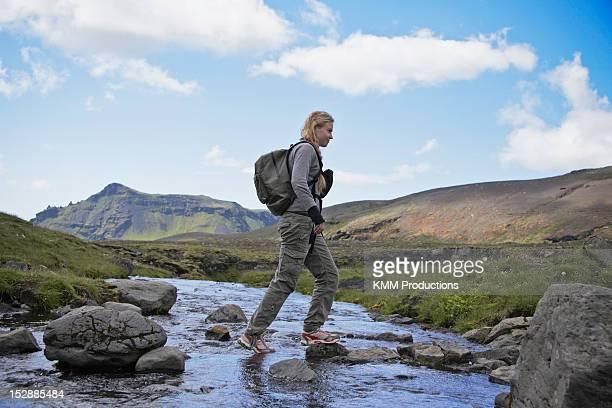 Hiker crossing rocky rural stream