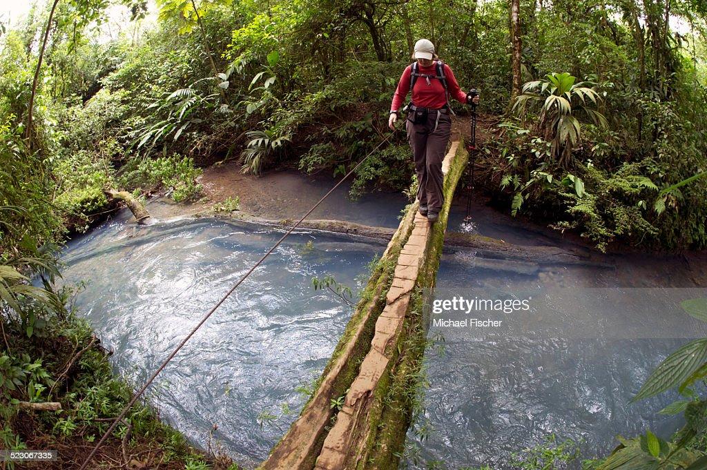 Hiker crossing the Rio Celeste on a wooden bridge, Tenorio National Park, Guanacaste, Costa Rica, Central America : Foto de stock
