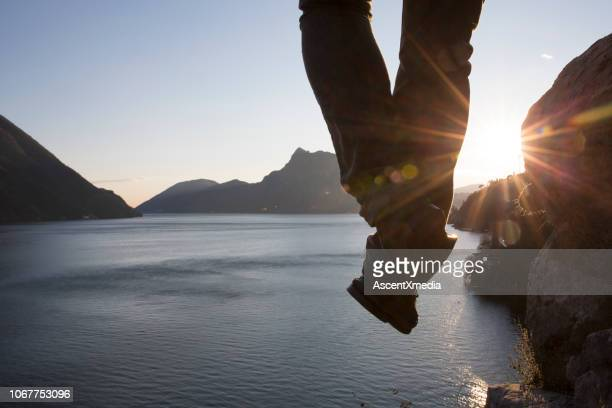 hiker dangles legs above lake surface - human limb stock pictures, royalty-free photos & images
