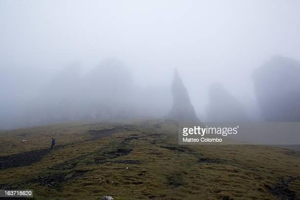 Hiker descending slope in the mist