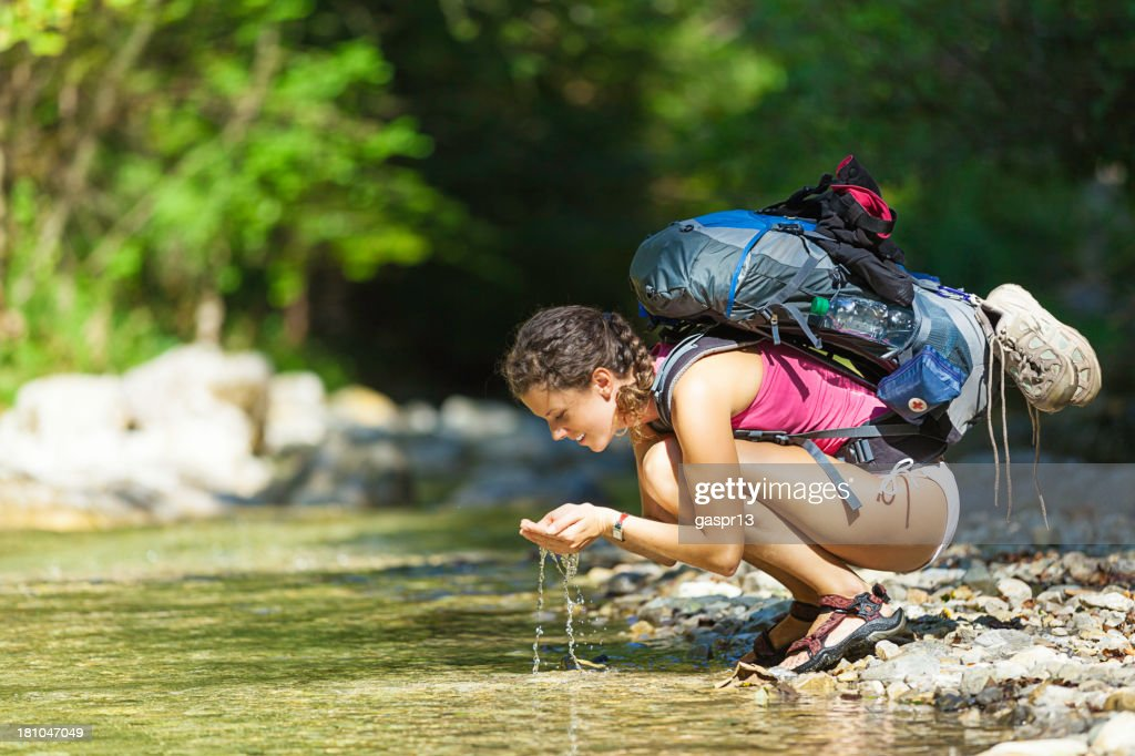 hiker drinking water from river : Stock Photo