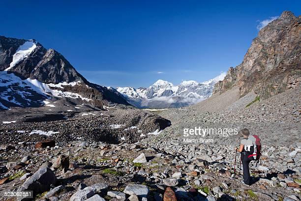 Hiker during ascent of Mt Tschenglser Hochwand above Duesseldorfer Huette hut in Sulden, Mt Vertainspitze, Mt Koenigsspitze and Mt Zebru at back, Suldental valley, South Tyrol, Italy, Europe
