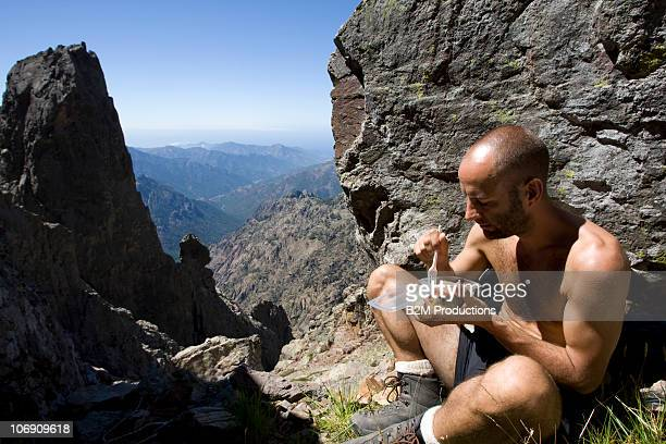Hiker eating on top of mountains