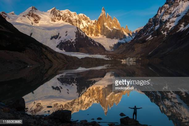 hiker enjoying scenic view of mountains and lake - los glaciares national park stock pictures, royalty-free photos & images