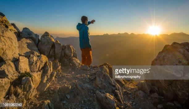 wanderer genießen sonnenaufgang auf einem berggipfel - tal stock-fotos und bilder