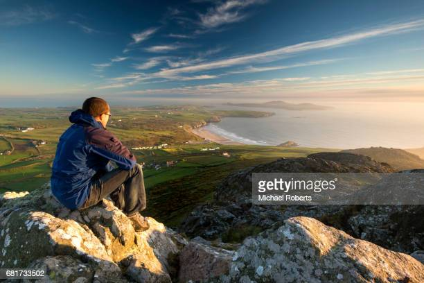 hiker enjoying the view from carn llidi towards whitesands bay and whitesands beach on the pembrokeshire coast path, wales - wales stock-fotos und bilder