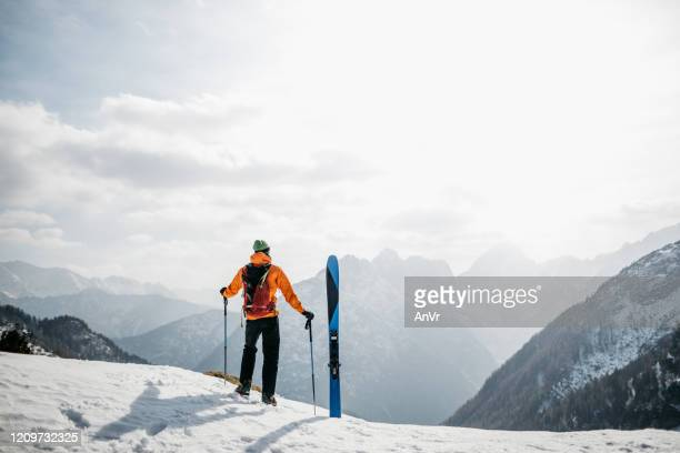 hiker enjoying the views in the mountains before skiing back to the valley - winter sport stock pictures, royalty-free photos & images