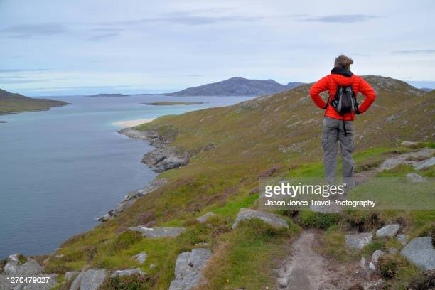a hiker enjoys the view on harris - coastline stock pictures, royalty-free photos & images