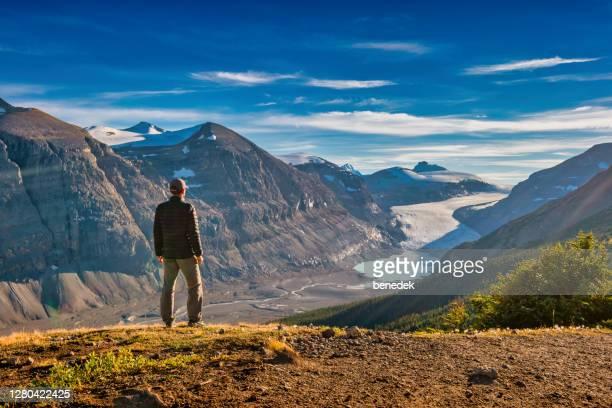 ハイカーはバンフ国立公園パーカーリッジサスカチュワン氷河の景色を楽しんでいます - ロッキー山脈 ストックフォトと画像