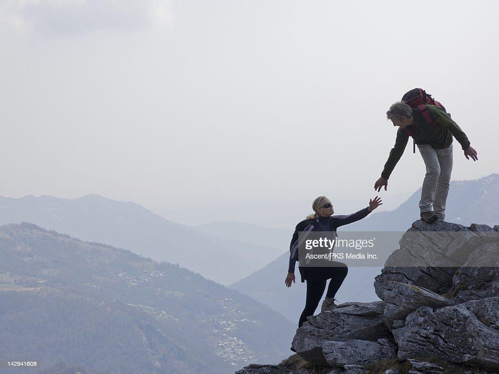 Hiker extends helping hand to partner, rock ridge : Stock Photo