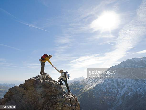 hiker extends helping hand to teammate, on ridge - climbing stock pictures, royalty-free photos & images