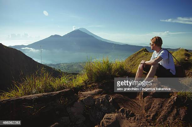 hiker facing a volcano mount agung, bali, indonesi - hand on knee stock pictures, royalty-free photos & images