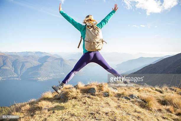 hiker female celebrates success on mountain top - lake bottom stock photos and pictures